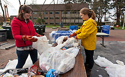 Savannah Phalan '15, right, and Sarah Wheeler 15, work on a table of trash during Garbology on Red Square, where grash from different locations is sorted to determine how much is recycleable or compostable at PLU on Tuesday, March 17, 2015. (Photo: John Froschauer/PLU)