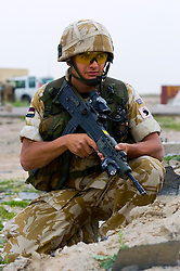 British soldier from the Royal Dragoon Guards wearing desert camouflage, Kevlar helmet and body armor, carrying SA80 assault rifle which is fitted with SUSAT sights, near Umm Qasr during Op-Telic in March 2005
