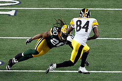 Feb 6, 2011; Arlington, TX, USA; Pittsburgh Steelers wide receiver Antonio Brown (84) breaks the tackle attempt of Green Bay Packers safety Atari Bigby (20) during the first half of Super Bowl XLV at Cowboys Stadium.  Green Bay defeated Pittsburgh 31-25.