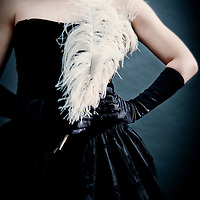 Young woman with short brown hair wearing black period party dress holding white feather