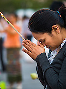 01 JANUARY 2016 - BANGKOK, THAILAND:          A woman prays with incense sticks during the annual New Year's mass merit making ceremony on at Sanam Luang in Bangkok. The ceremony is sponsored by the Bangkok city government. More than 500 Buddhist monks participated in the ceremony this year. Thais usually go to temples and religious observances to meditate and make merit on New Year's Day.      PHOTO BY JACK KURTZ