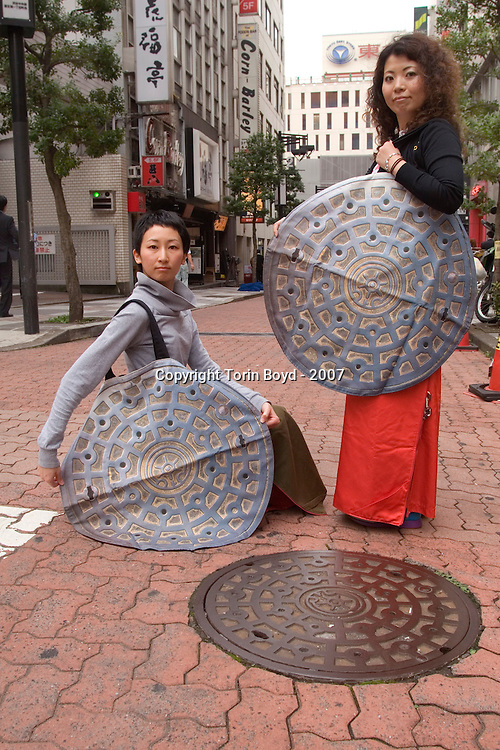This is the creation of 29 year old Aya Tsukioka, an imaginative clothing designer who teaches at Musashino Art University in Tokyo. One of her designs seen here, is a shoulder bag that mimics a manhole cover. The purpose of this accessory is security, enabling the user to conceal items by quickly camouflaging them on the street. Other items Tsukioka has created is a long skirt that transforms to mimic the facade of a Coke vending machine, should the wearer be pursued; and a child's school backpack that mimics a Japanese fire hydrant. Tsukioka is seen here (long wavy hair) modeling her bag in the Shibuya district of Tokyo, along with Minako Ogawa, 29, of Tokyo who's a dancer.