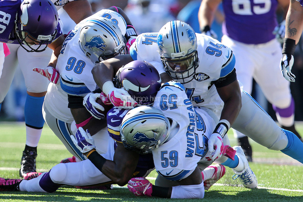 Oct 12, 2014; Minneapolis, MN, USA; Minnesota Vikings running back Jerick McKinnon (31) is tackled by Detroit Lions defensive tackle Nick Fairley (98), linebacker Tahir Whitehead (59) and defensive end Ezekiel Ansah (94) during the first quarter at TCF Bank Stadium. The Lions defeated the Vikings 17-3. Mandatory Credit: Brace Hemmelgarn-USA TODAY Sports