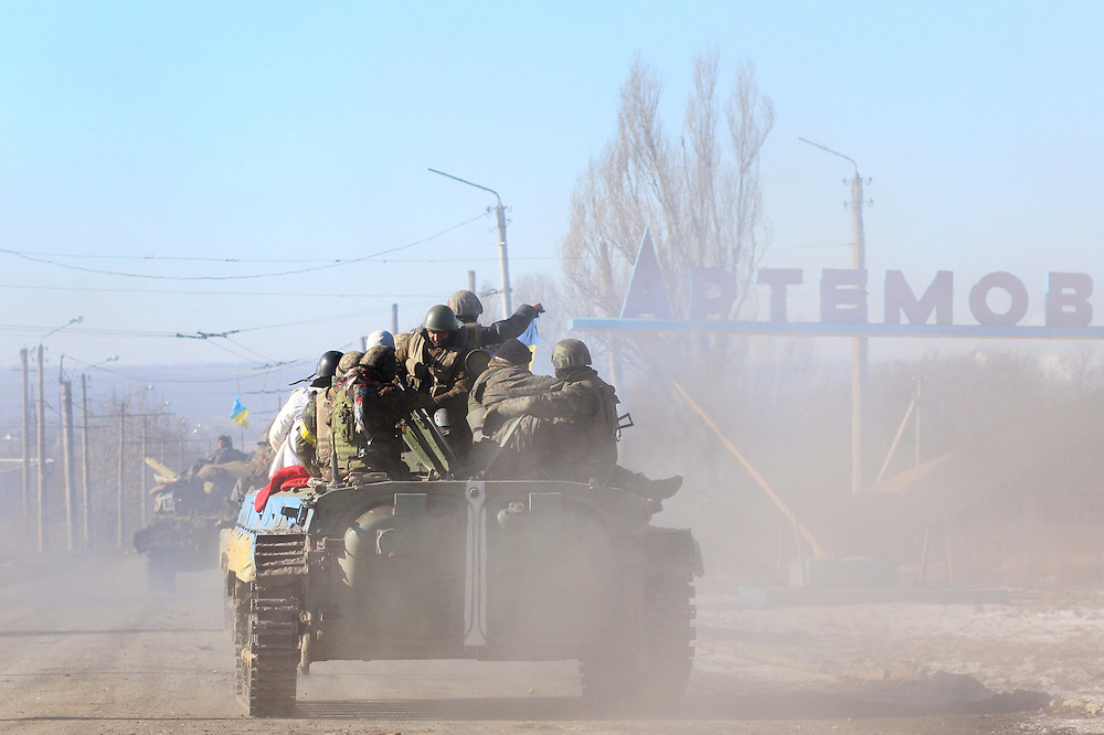 Armored vehicles, including a tank and APCs, depart towards Artemivsk on February 18, 2015 on a road about 40 kilometers from Debaltseve, Ukraine. The soldiers had withdrawn from Debaltseve earlier in the day and were regrouping at a crossroads before heading towards Artemivsk.