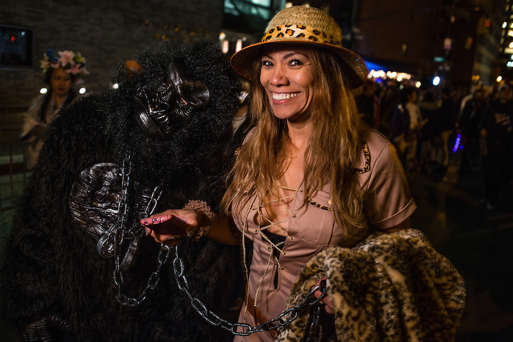 New York, NY - 31 October 2016. A woman in a safari outfit leads a gorilla on a chain  in the Greenwich Village Halloween Parade.