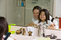Mother and Daughter Looking at reflection in Bathroom mirror focus on mirror