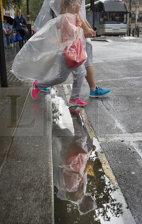 © Licensed to London News Pictures. 02/08/2016. London, UK. Tourists wearing plastic ponchos are reflected in a puddle as intermittent rain showers hit the capital. Photo credit: Peter Macdiarmid/LNP