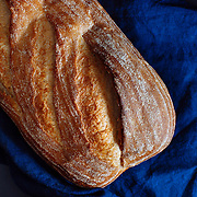 Sourdough loaf of bread with a indigo napkin on a slate board black background