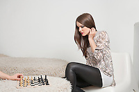 Beautiful young woman playing chess