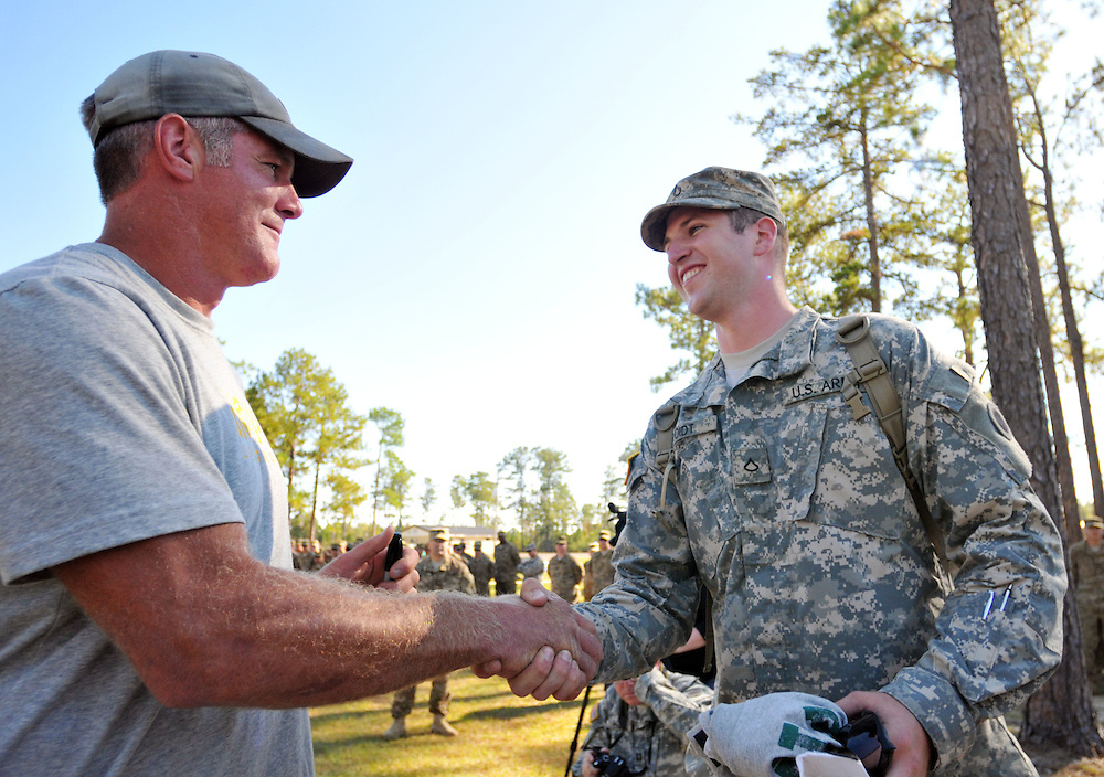 "Football legend Brett Favre shakes hands with PFC Robert Roidt Tuesday while visiting troops from the Ohio National Guard's 1stBattalion of the 134th at Camp Shelby military post before they deploy to Afghanistan over the next few days. ""I've been a fan for a long time,"" said Roidt as Favre signed a t-shirt for him. ""Thanks. I've been playing for a long time,"" responded Favre. Bryant Hawkins/ Hattiesburg American"