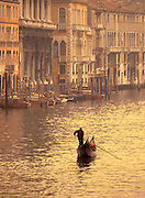 Image of a gondolier rowing his gondola along the Grand Canal of Venice, Italy