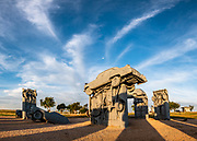 """Carhenge sunrise. Carhenge replicates England's Stonehenge using vintage American automobiles, near Alliance, Nebraska, in the High Plains region, USA. After studying Stonehenge in England, years later, Jim Reinders recreated the physical size and placement of Stonehenge's standing stones in summer 1987, helped by 35 family members. Reinders said, """"It took a lot of blood, sweat, and beers."""" Carhenge was built as a memorial to Reinders' father. 39 automobiles were arranged in the same proportions as Stonehenge with the circle measuring a slightly smaller 96 feet (29m) in diameter. Some autos are held upright in pits five feet deep, trunk end down, while other cars are placed to form the arches and welded in place. All are covered with gray spray paint. The heel stone is a 1962 Cadillac. Reinders donated Carhenge to the Friends of Carhenge, who gifted it to the Citizens of Alliance in 2013. This image was stitched from multiple overlapping photos."""