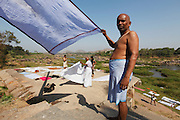 A man drys his sari after having washed it in the river. Founded in 1336, Vijayanagar was the capital of an alliance of southern Hindu kingdoms that ruled southern India for hundreds of years and left a sprawling architectural wonderland of magnificent temple ruins set amongst an otherworldly landscape of gigantic sandstone boulders, meandering streams and banana plantation near the village of Hampi in the state of Karnataka. The temples, spread over an area of 25 square kilometers and 58 of its 550 buildings were declared UNESCO World Heritage Sites in 1986. Other than the Taj Mahal, no other monument in India is written about as much as Hampi. But the millions of visitors who visit those other architectural sites have yet to show serious interest in Hampi, which is remote, lacks infrastructure and is hardly publicized.