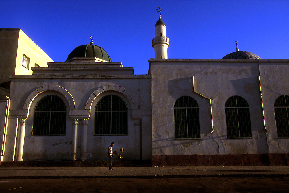 A young man plays football outside the Al Qurafi al Rashidin Mosque ('Followers of the Right Path') built in 1937 by Italian architects, Asmara, Eritrea..