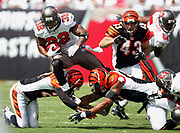 TAMPA, FL - OCTOBER 15:  Running back Michael Pittman #32 of the Tampa Bay Buccaneers goes airborne as he leaps over two Cincinnati Bengals tacklers at Raymond James Stadium on October 15, 2006 in Tampa, Florida. The Bucs defeated the Bengals 14-13. (©Paul Anthony Spinelli) *** Local Caption *** Michael Pittman