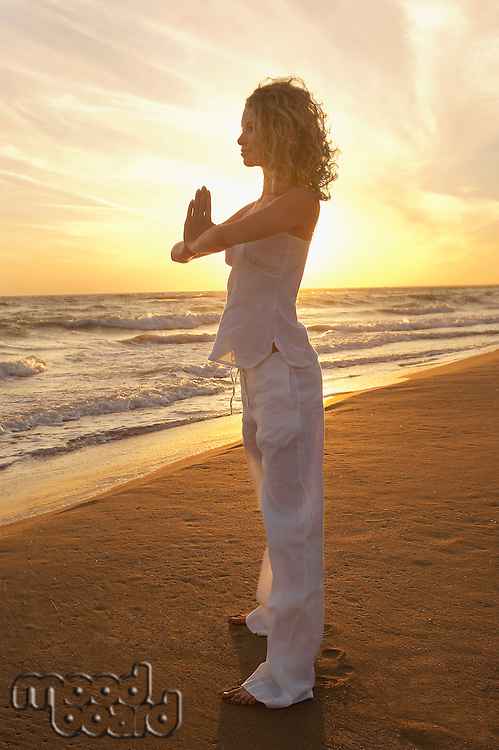 Young woman doing Tai Chi on beach side view
