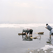 A worker with a water hose tries to tame an iceberg of foam form Chimical Waste dumped by factories along the Yamuna river.