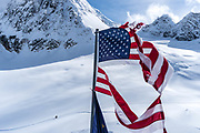 This flag at the Sheldon Mountain house gets chewed up with the wind.  Mount Dicky in the background and a climber on the trail up.