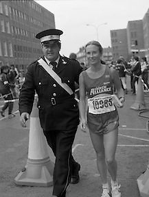 Finish of Dublin City Marathon .25/10/1982  Radio 2, Dublin City Marathon..1982.25.10.1982.10.25.1982.25th October 1982..The Radio 2 sponsored Dublin City Marathon finish at St Stephens Green Dublin..The overall winners were:Men, Gerry Kiernan,Listowel, Kerry. Women, Debbie Mueller,U.S.A. and the first wheelchair competitor Michael O'Rourke..A St Johns Ambulance man escorts debbie Mueller to the reception area.