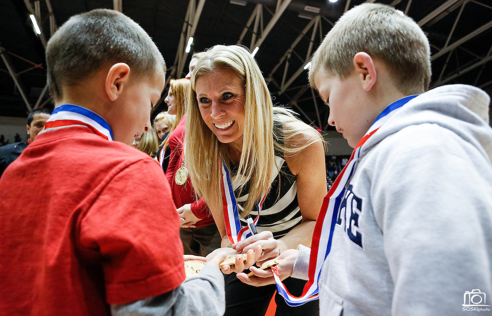 Coppell's head coach, Julie Green, compares her first place medals with her sons, Briggs (7), left, and Maddox (8), right, after beating New Braunfels in the Class 5A state championship at the Curtis Culwell Center in Garland, Texas, on November 17, 2012.  (Stan Olszewski/The Dallas Morning News)
