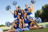 Cheerleaders posing on lawn (portrait)