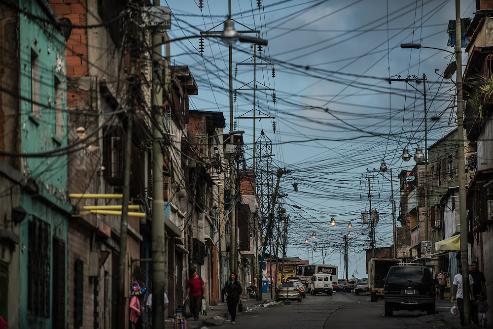 CARACAS, VENEZUELA - MAY 20, 2016:  People walk under power lines in Catia, a slum in western Caracas. Despite having the largest known oil reserves in the world, the Venezuelan government is having difficulties providing basic services like electricity and running water. They are currently rationing both. Most emblematic has been perhaps one of the most desperate measures ever by a government to save electricity: A shut down of nearly all government buildings to all but two (part-time) days each week. Government employees in Venezuela only go to work now on Mondays and Tuesdays.  All public schools now have a three-day weekend, taking off Fridays in order to save electricity.  PHOTO: Meridith Kohut for The New York Times