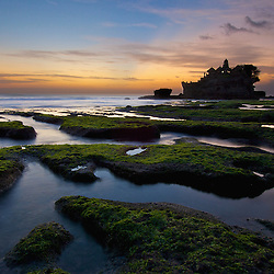 Low tide reveals the shallow reef near the Balinese temple of Tanah Lot. Tanah Lot seaside temple is one of Bali's most important Hindu temples.