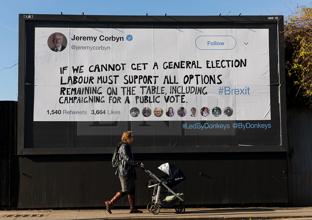"© Licensed to London News Pictures. 14/02/2019. London, UK.  A woman with a pram walks past a new Jeremy Corbyn billboard from ""Led By Donkeys"" that has been put up in Mr Corbyn's Islington constituency with a message asking for Labour party support on a pubic vote on Brexit. A previous billboard, errected in the same place on Monday was reportedly removed by Islington Council, who later replaced the blank board when challenged. Photo credit: Vickie Flores/LNP"