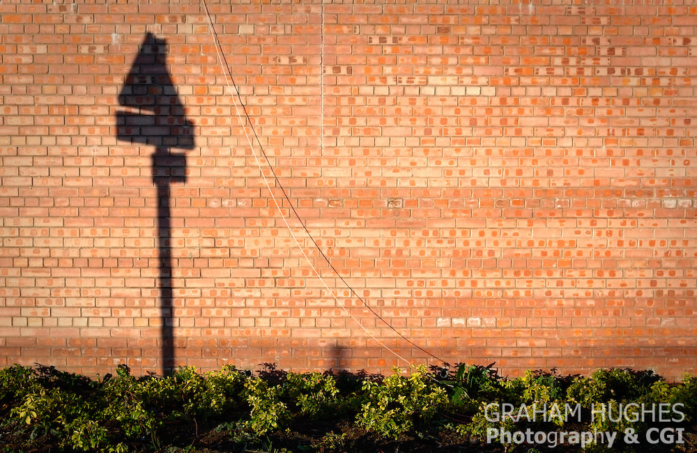 Brick wall with road sign's shadow on it. Green plants growing at bottom of wall. Early morning light.
