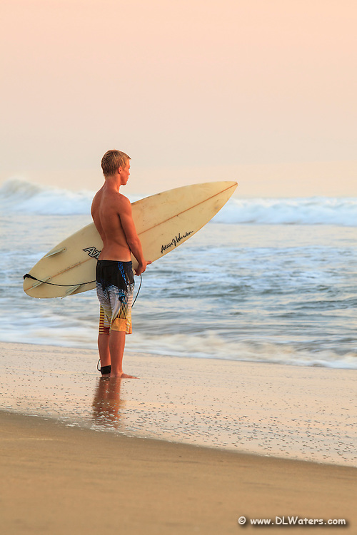 A young surfer waiting on the waves.