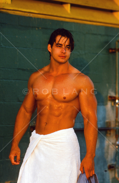 muscular man wrapped in a towel after taking an shower outdoors