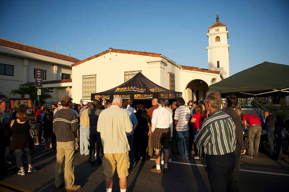 A small crowd outside the Fullerotn Police Department gathers for the KFI radio John and Ken Show, being broadcast live.