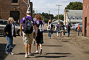Senior football players walk to the weight room after school while fellow students wish them luck.