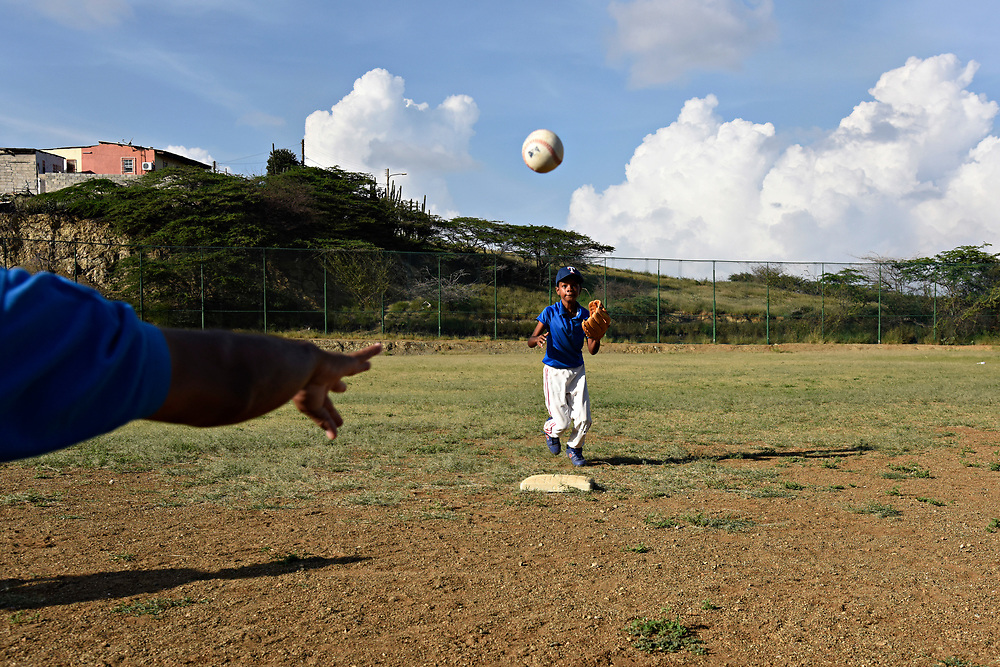 WILLEMSTAD, CURACAO - DECEMBER 11, 2014: Many people attribute the good shortstops that Curacao produces to the crummy fields they learn on, where bad bounces are the norm. Here, Brandon Pina, 10, gets practice playing second for his Marchena Hardware team at Parke Shon Ki Nicasia in Willemstad. (photo by Melissa Lyttle)