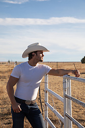 profile of a cowboy leaning on a rustic fence