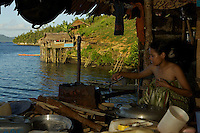 Semi-permanent fishermans camp at Tanjung Besi, Gam Island.  These outsiders from Buton Island, Sulawesi, come here for moths at a stretch to fish at night for small fish...This view is inside one of the huts on stilts over the water where a woman is preparing rice and fish for men preparing to go out fishing for the night.  The jerrycans are their water supply, which must be hauled from a spring.