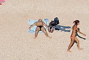 Man at the beach, young woman passing, Sardegna
