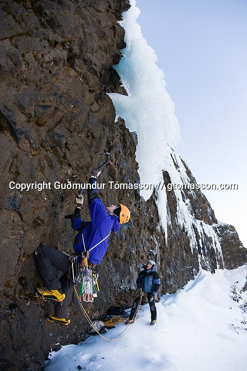 """Róbert Halldórsson, Sigurður Tómas Þórisson on belay, on the first ascent of the ice climb """" Stálin stinn"""" WI5/M6, 100m, at Tröllhamrar, Breiðdalur. East Iceland."""