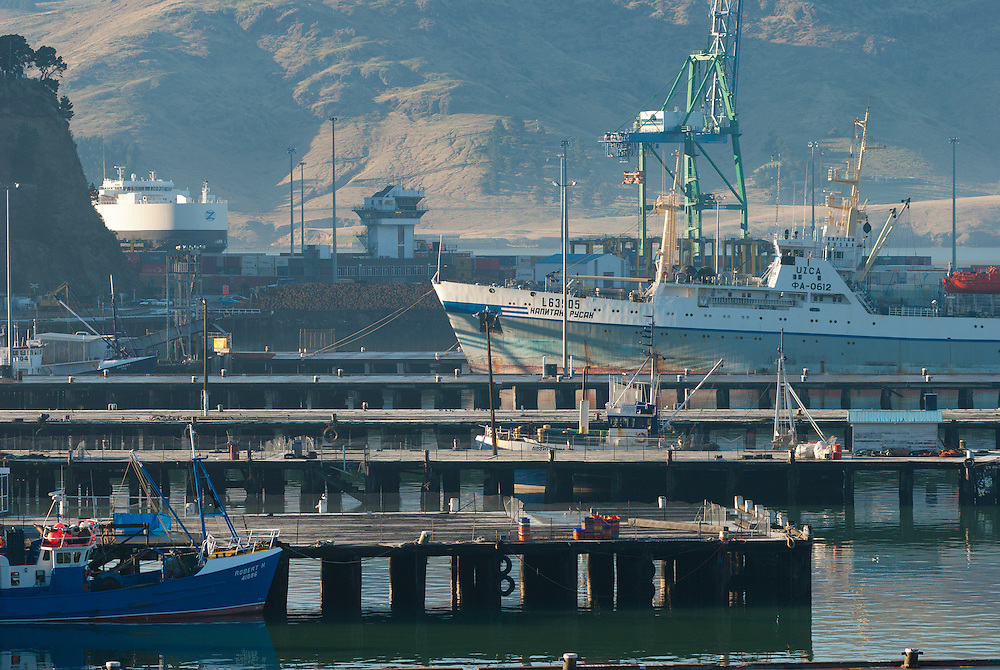 Telephoto view of a large Eastern European fishing vessel moored at LPC wharf, Lyttelton NZ. Hazy morning sunlight casts shadows on distant mountains with a small blue boat berthed bottom left.