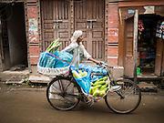 01 AUGUST 2015 - KATHMANDU, NEPAL: A fruit and produce vendor pushes his bike with his merchandise through central Kathmandu.      PHOTO BY JACK KURTZ