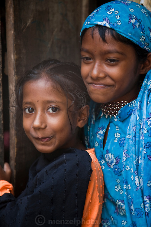 The children of one of Shahnaz Hossain Begum's neighbors at their home in Bari Majlish village outside Dhaka, Bangladesh.   (Shahnaz Hossain Begum is featured in the book What I Eat: Around the World in 80 Diets.)   Shahnaz got her first micro loan several years ago, from BRAC, Bangladesh Rehabilitation Assistance Committee, to buy cows to produce milk for sale. She repaid her initial loan and has since gotten new ones over the years along with thousands of her fellow Bangladeshis. This mother of four was able to earn enough to build several rental rooms next to her home. She and her tenants share a companionable outdoor cooking space and all largely cook traditional Bangladeshi foods such as dahl, ruti (also spelled roti), and vegetable curries. She and her family don't drink the milk that helps provide their income.