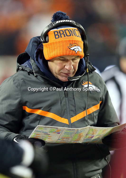 Denver Broncos head coach Gary Kubiak looks down at his play chart on the sideline during the 2015 NFL week 16 regular season football game against the Cincinnati Bengals on Monday, Dec. 28, 2015 in Denver. The Broncos won the game in overtime 20-17. (©Paul Anthony Spinelli)