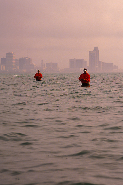 Stock photo of two men wading into the bay to fish with the Corpus Christi skyline in the background