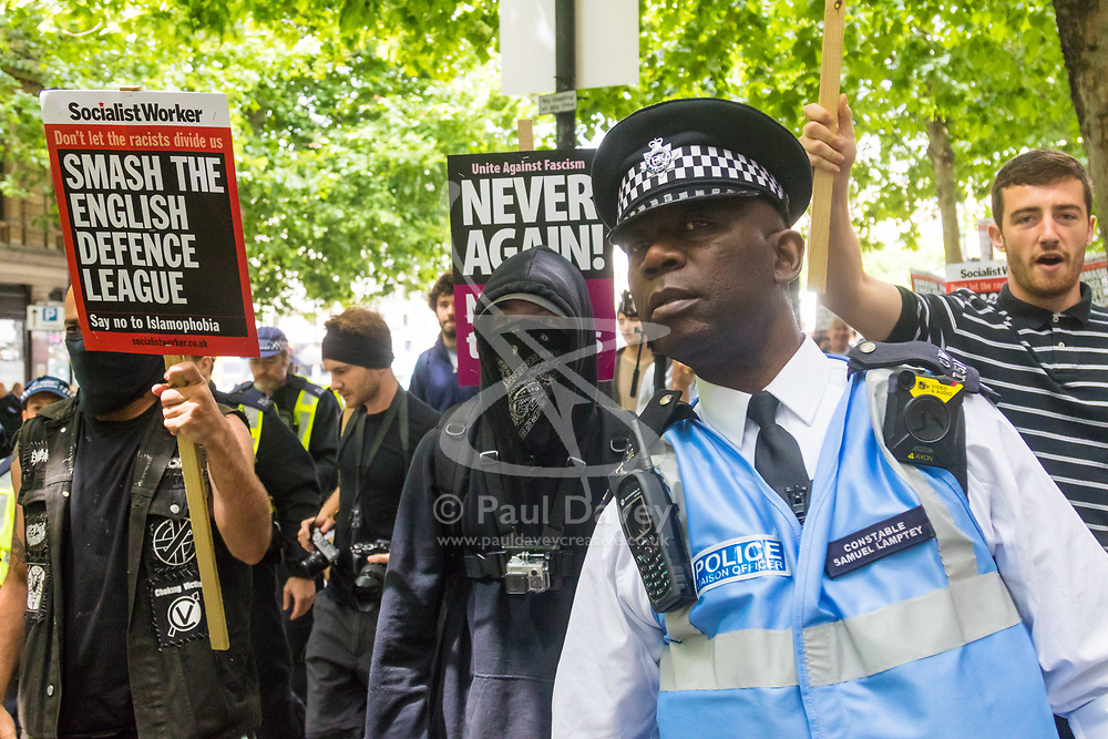 London, June 24th 2017. Anti-fascist protesters counter demonstrate against a march to Parliament by the far right anti-Islamist English Defence League. PICTURED: Masked anti-fascists chant their slogans at retreating EDL supporters following a scuffle near Trafalgar Square.
