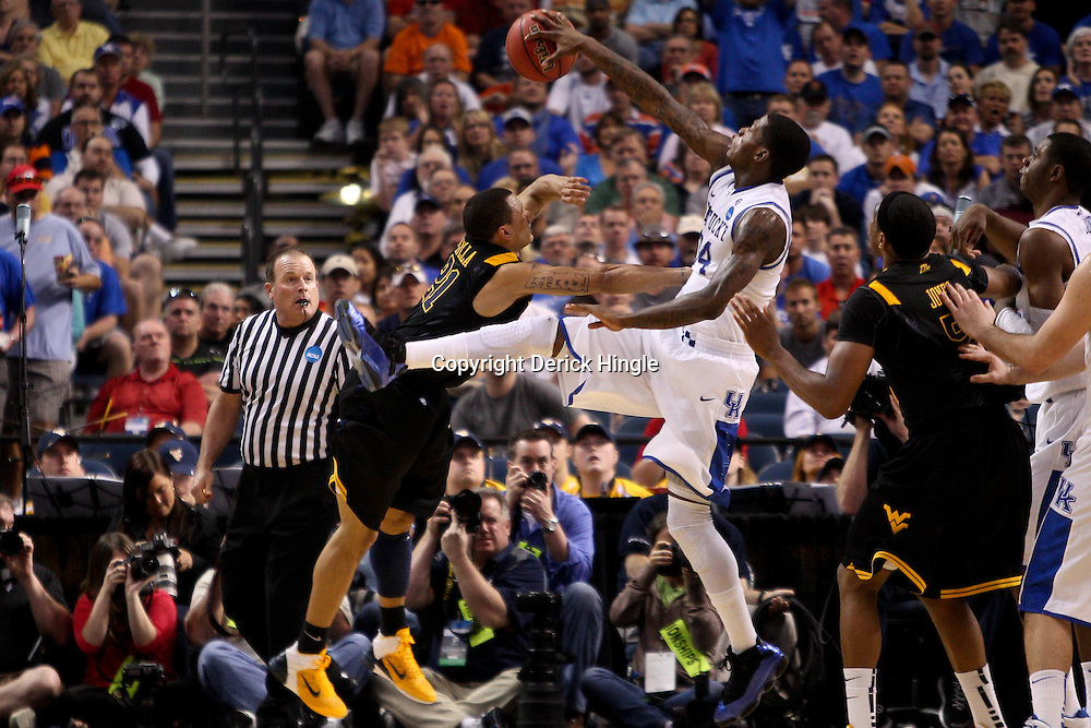 Mar 19, 2011; Tampa, FL, USA; Kentucky Wildcats guard DeAndre Liggins (34) blocks a shot by West Virginia Mountaineers guard Joe Mazzulla (21) during the second half of the third round of the 2011 NCAA men's basketball tournament at the St. Pete Times Forum. Kentucky defeated West Virginia 71-64.  Mandatory Credit: Derick E. Hingle