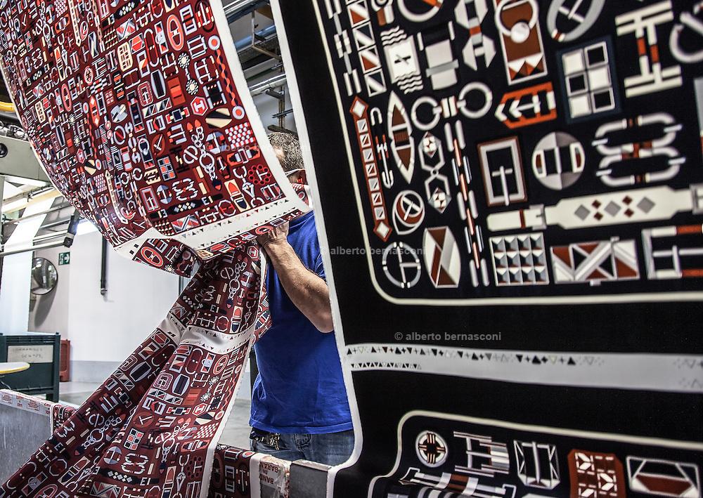 Lyon, Atelier Hermès, silk atelier at Pierre-Benite, Dopo la fase di stampa, il lungo rullo di twill di seta dei carrés esce dalla macchina del vapore e dell'appretto. I carrés non sono stati ancora separati l'uno dall'altro. a long roll of silk coming out from the steam machine. The carré will be separate soon