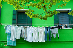 Laundry hanging outside olourful houses in village of Burano near Venice in Italy