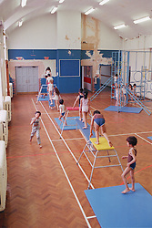 Junior school children using equipment in school sports hall during Physical Education lesson,