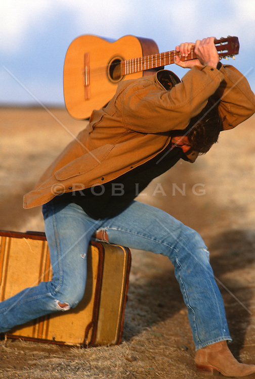 Man swinging a guitar over his head while seated on a suitcase in the middle of nowhere