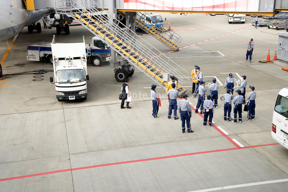 cleaning crew waiting to enter a passenger airplane at Narita International airport Tokyo Japan